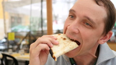 Young man guy eating chewing a piece of pizza in Rome street restaurant in Italy Stock Footage