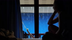 Sad lonely girl sitting by the window and looks outside while rain goes. - stock footage