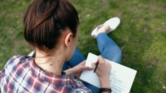 Young woman in casual clothes with tattoo on neck writing in her journal sitting - stock footage