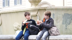 Kids tourists sit and rest eating sandwiches during walking tour in Rome Italy Stock Footage
