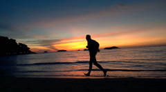 Silhouette of man running on beach during sunset, super slow motion 120fps Stock Footage