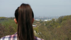 Close-up of young brown haired woman in checkered shirt standing back to the Stock Footage