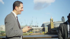4K Smart London Businessmen using mobile technology outdoors in the city Stock Footage