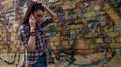 Young woman with speaking on cell phone and touching her brown hair while - stock footage