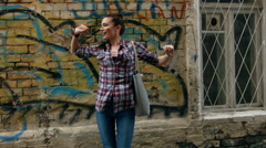 Young woman  in checkered shirt and blue jeans dancing against wall with Stock Footage