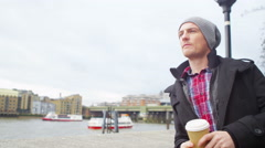 4K Man on his own in London, drinking coffee and looking out at view over river Stock Footage