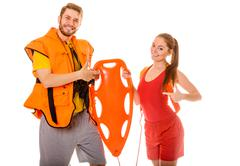 Lifeguards in life vest with rescue buoy. - stock photo
