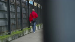 4K Serious man walking alone, away from railway station Stock Footage