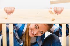 Happy woman assembling wood furniture. DIY. Stock Photos