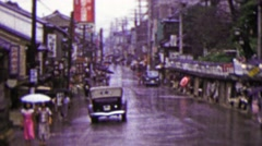 1951: Busy Japanese commercial street raining umbrellas drawn. Stock Footage
