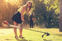 Girl with grass cutter in park. Kuvituskuvat