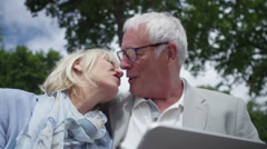 4K Fun attractive mature couple looking at computer tablet in the city - stock footage