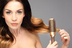 Laying, modeling hair on a round brush. Stock Photos