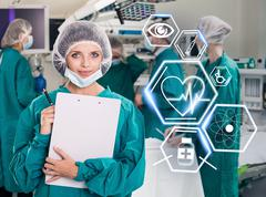 Surgery team with futuristic healthcare icons - stock photo