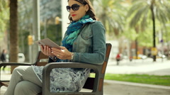 Woman sitting on the bench in the city and using smartphone, steadycam shot Stock Footage