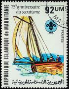 Sailing boat with scouts on postage stamp - stock photo