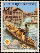 Canoe with scout in Aboriginal village on postage stamp - stock photo