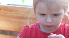 Little girl is eating at table Stock Footage