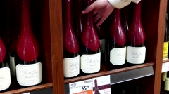 A hand takes bottle of Pinot noir belle glos clark red wine from the shelf - stock footage