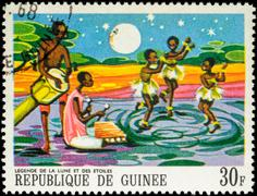 Three dancing black girls - scene from African Legends on postage stamp Stock Photos
