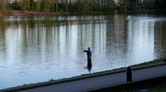 Motion of man fishing at Lafarge lake in Coquitlam Stock Footage