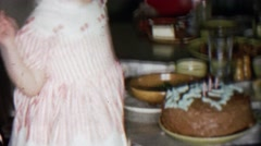 1956: Toddler girl blowing out birthday cake candles proud parents watch. Stock Footage