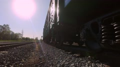 Freight train awaiting in the industrial district, carries green containers. Stock Footage