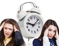 Women with a headache and alarm clock Stock Photos