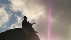 Man playing guitar on the cliff silhouette slow motion follow focus Stock Footage