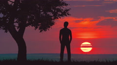 The man stand near the tree against the bright sunset Stock Footage