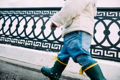 little boy walks through the puddles in the street - stock photo