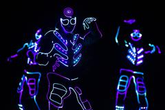 Dancers crew in led suits on dark background, colored show Stock Photos
