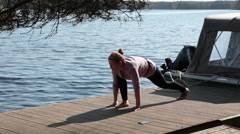 Attractive woman doing one of asana of yoga on wooden pier at lake Stock Footage