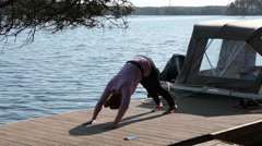 Sporty woman doing exercices on wooden pier with moored speedboat, forest lake Stock Footage
