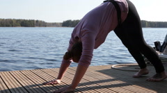 Fitness and yoga exercises on lake shore, young woman loses weight Stock Footage