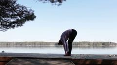 Serene Caucasian woman doing yoga on nature at lakeshore Stock Footage
