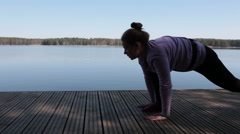 Casual attractive woman doing yoga on the lake shore Stock Footage