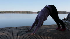 Pretty Caucasian woman practicing yoga outdoor on lake pier Stock Footage