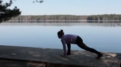 Rear side view of attractive woman doing yoga poses on wooden pier Stock Footage