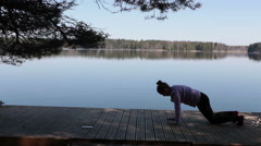 Sportswoman doing yoga exercises on wooden pier of forest lake Stock Footage