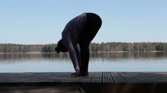 Attractive Caucasian woman standing on wooden pier in yoga pose on lake Stock Footage