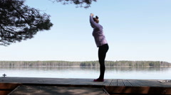 Sportswoman practicing yoga at morning near the forest lake shore Stock Footage