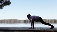 Caucasian sportswoman practicing yoga at morning on lake shore Stock Footage