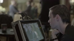 The Director oversees the shooting of the film in the monitor. Filmmaking Stock Footage