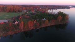 Orange coloring trees on the lake shore at early morning at sunrise. Aerial view Stock Footage