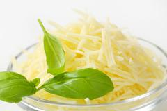 Heap of grated cheese in a glass bowl - stock photo