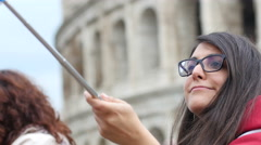 Coliseum - Girl tourist take selfie photo via phone on stick by Colosseum Rome Stock Footage