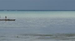 White beach at Zanzibar with sailing fisherman Stock Footage