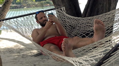 Young man using smartphone lying on hammock on beach Stock Footage