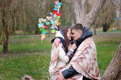 Couple in love under blanket is heated autumn park Stock Photos